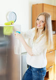 Positive blonde woman cleaning  glass Royalty Free Stock Image