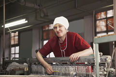Positive blonde woman with comb at the factory Stock Photography