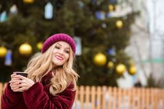 Positive blonde woman drinking coffee near the Cristmas tree on Royalty Free Stock Image