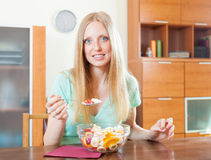 Positive  blonde woman eating  fruit salad Royalty Free Stock Photography