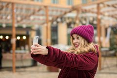 Positive blonde woman having fun and making self portrait at the Royalty Free Stock Photo