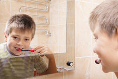 Positive boy brushing teeth reflection Royalty Free Stock Photography