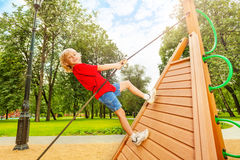 Positive boy climbs on wooden construction Stock Image