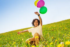 Positive boy with flying balloons in summer Royalty Free Stock Photo