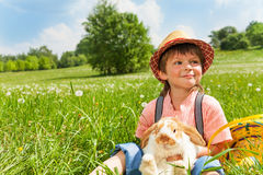 Positive boy with hat hugging rabbit in summer Stock Photos