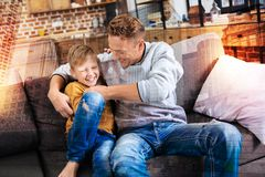 Positive boy laughing while his smiling father tickling him. Tickle. Joyful little boy sitting at home on a comfortable sofa and laughing while his father royalty free stock photos