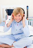 Positive boy listening music sitting on bed Stock Photography