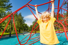 Positive boy with straight hands hangs on rope Royalty Free Stock Images