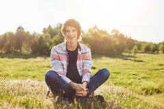 Positive boy with trendy hairstyle wearing shirt and jeans sitting crossed legs on greenland having good mood smiling while posing. Into camera relaxing at Royalty Free Stock Images