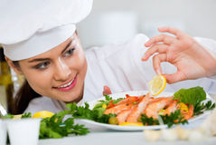 Positive brunette chef arranging shrimps Stock Photo
