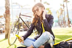 Positive brunette girl in sunglasses in sinlight is sitting on grass on bike and palms background. She is using yellow.  stock images