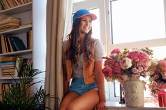 Positive brunette woman in a room. Positive brunette woman in a room with books stands and flowers bouquet close to a window Stock Images