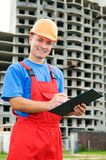Positive builder worker. Smiley happy builder worker with cardboard at building construction area Royalty Free Stock Photos