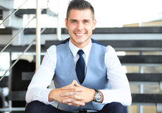 Positive business man sitting on stairs of modern office Royalty Free Stock Photography