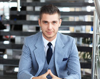 Positive business man sitting on stairs of modern office Royalty Free Stock Photo