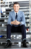 Positive business man sitting on stairs of modern office Royalty Free Stock Photos