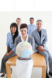Positive business people holding a terrestrial glo. Positive international business people holding a terrestrial globe in the office stock photos