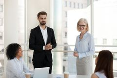 Positive business people in office during meeting. Mature female company owner introducing investor or coach experienced consultant business trainer to diverse royalty free stock photography