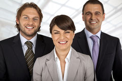 Positive business team of three. Business team of three, female in front, two males behind, all smiling stock images