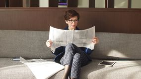 Positive business woman holding newspaper and resting after work. Free time, hobby, lifestyle stock video