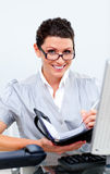 Positive business woman writting on her agenda Stock Images