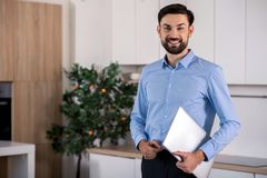 Positive businessman holding his laptop royalty free stock image