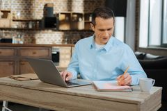 Positive businessman preparing his project. Working process. Delighted brunette keeping smile on his face and turning head while making notes Stock Photography