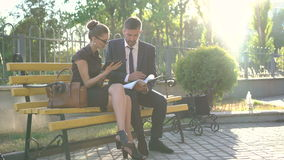 Positive businessman shaking hands with female partners on the bench. 4K.  stock footage