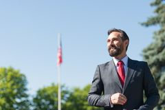 Positive businessman smiling and looking glad while being outdoors royalty free stock photo