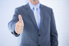 Positive businessman smiling with thumb up. Against stores Royalty Free Stock Photos