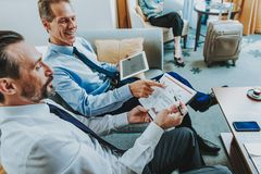 Positive businessman with tablet pointing to the graphic of his colleague royalty free stock photos