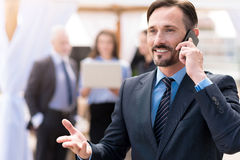 Positive businessman talking on cell phone Stock Photography