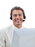 Positive businessman talking on headset. At a computer in the office Stock Photography