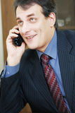 Positive businessman talking via phone Stock Photo