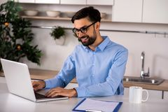 Positive businessman working on the laptop stock photos