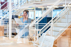Positive businesswoman on her phone in a modern creative office Royalty Free Stock Images