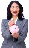 Positive businesswoman saving money in a piggybank. Against a white background Royalty Free Stock Photos
