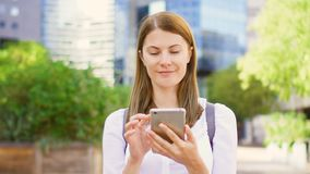 Smiling businesswoman in white shirt standing in downtown business district using smartphone. Positive businesswoman in white shirt smiling standing in downtown stock video