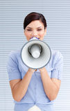 Positive businesswoman yelling through a megaphone Royalty Free Stock Photos