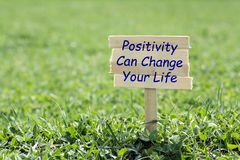 Positive can change your life. Wooden sign in grass,blur background royalty free stock photos