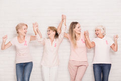 Positive cancer survivors. Wearing pink, holding each other hands royalty free stock photos