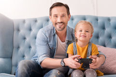 Positive caring father teaching his daughter to play video games Royalty Free Stock Image