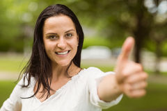 Positive casual brunette with thumbs up Stock Photography