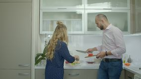 Cheerful casual couple preparing food in kitchen stock video