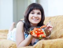 Positive casual woman eats  salad Royalty Free Stock Image