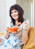 Positive casual woman eats veggie salad Stock Photography
