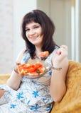 Positive casual woman eats veggie salad Stock Photography