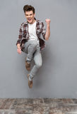 Positive casual young man jumping in the air and smiling. Positive delighted cheerfu carefree casual young man in plaid shirt and gray pants jumping in the air Stock Images