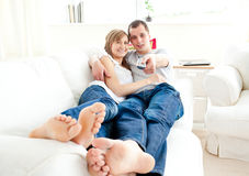 Positive caucasian couple lying on the couch Stock Photography