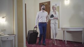 Positive Caucasian couple with travel bag entering hotel room and talking. Portrait of satisfied hotel guests arriving